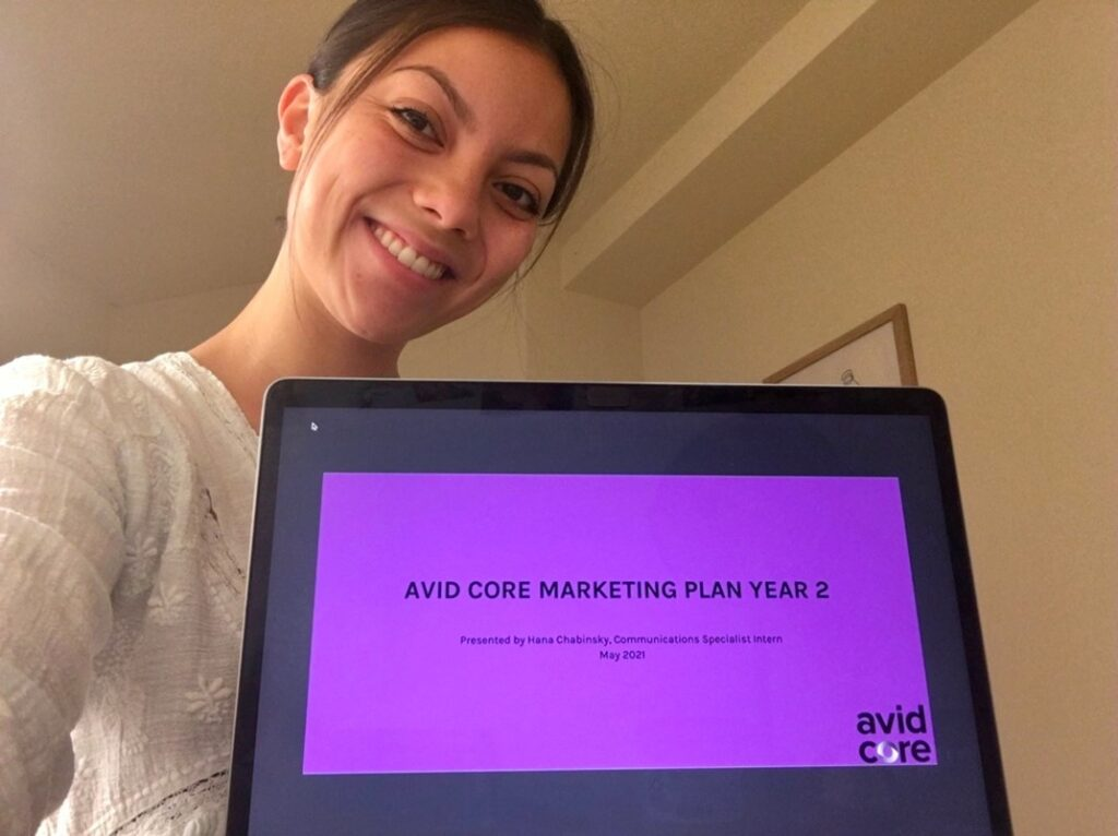 Spring intern, Hana Chabinsky, smiles for a selfie and shows the title page of her marketing plan.