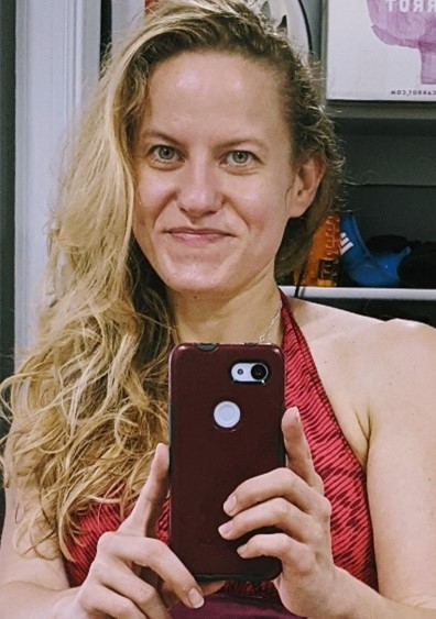 A blonde woman takes a photo of herself with her phone in front of a mirror.
