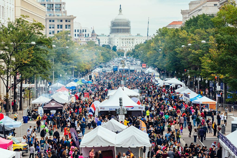 Patrons walking through various tented food stands on a narrow street. The United States Capitol sits at the end of the street.