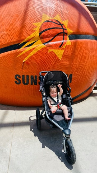 A baby sits in a stroller in front of a giant basketball. Phoenix Suns logo is painted on the basketball.