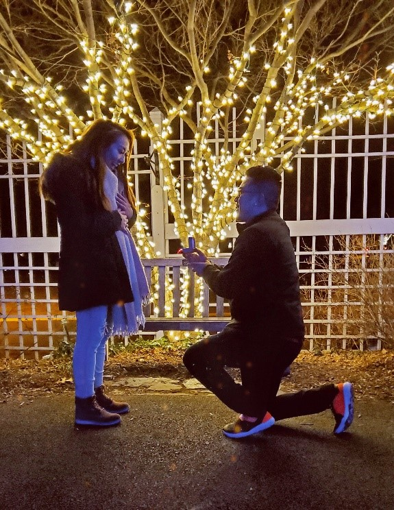 A man rests on one knee and proposes to a woman in front of Christmas lights at night