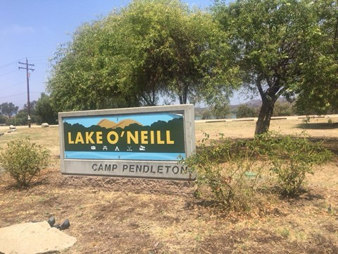 A sign of Lake O'Neill at Camp Pendleton is shown in front of two trees in desert land.